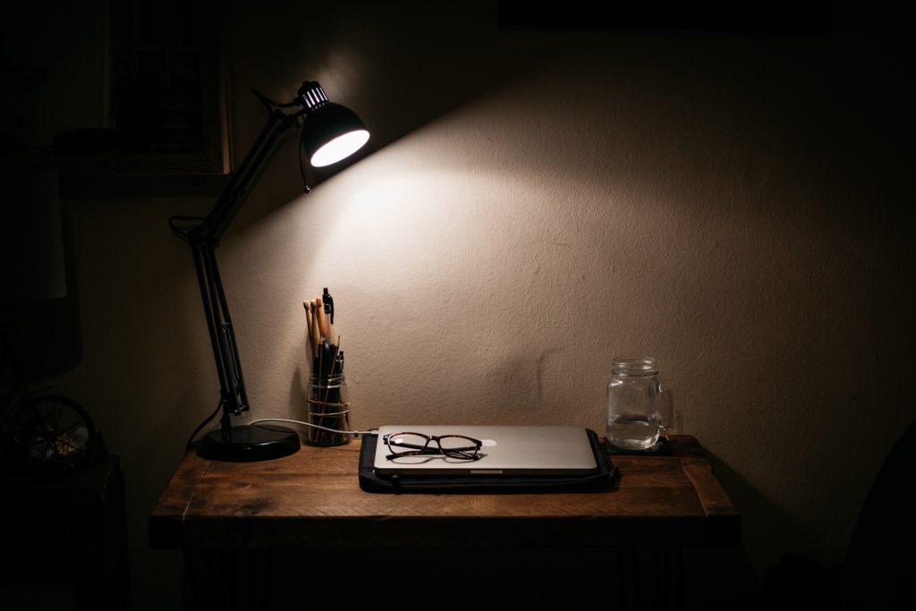 Desk lamp illuminating closed laptop